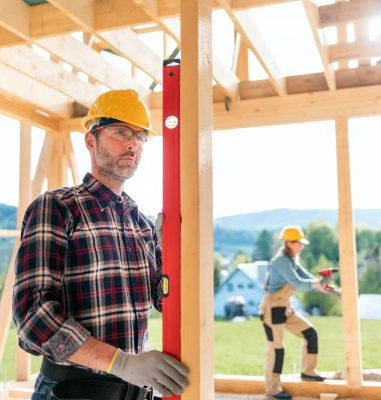 Worker measure construction on building site of frame house